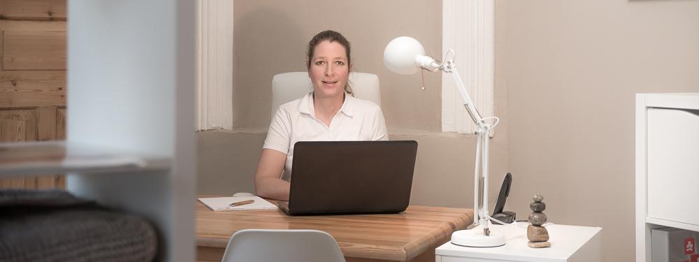 Heilpraktikerin Ilka Nossek sitzend hinter ihrem Schreibtisch